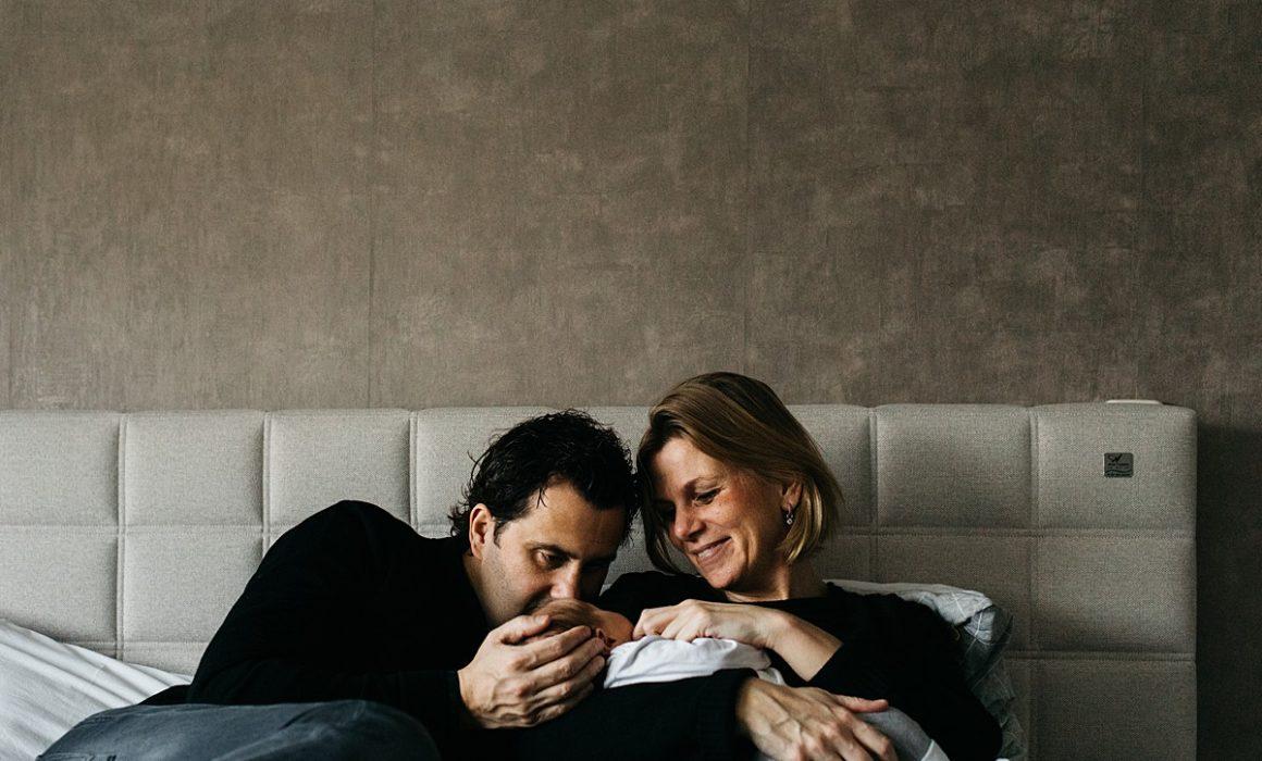 ouders op bed met newborn