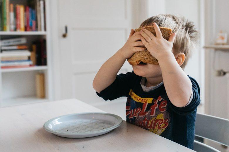 kind houdt brood voor zijn hoofd