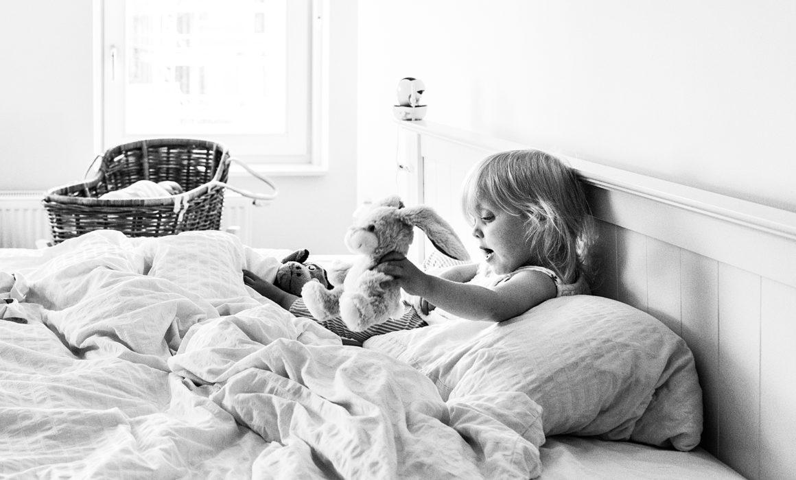 meisje speelt op bed van ouders