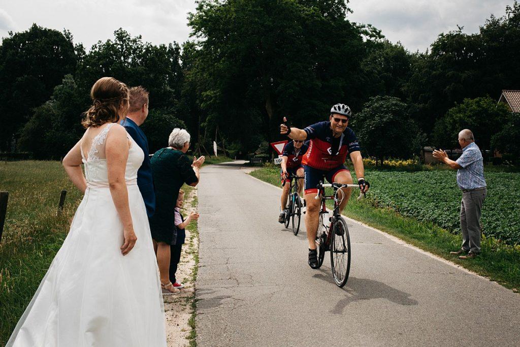 wielrenners rijden langs bruidspaar