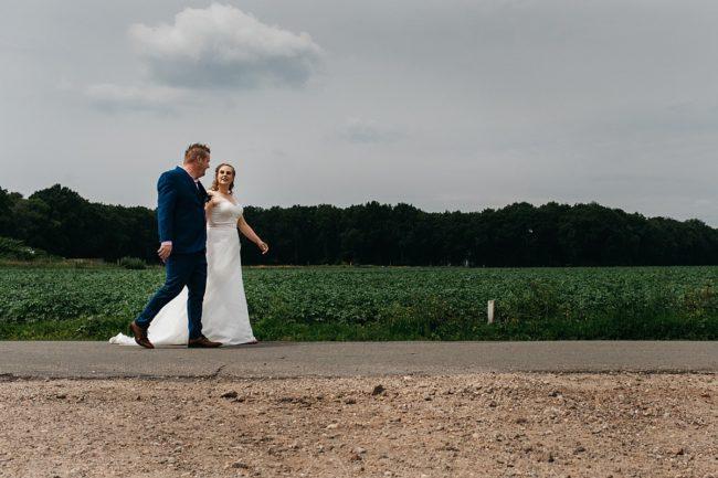 bruidspaar wandelt langs de weilanden