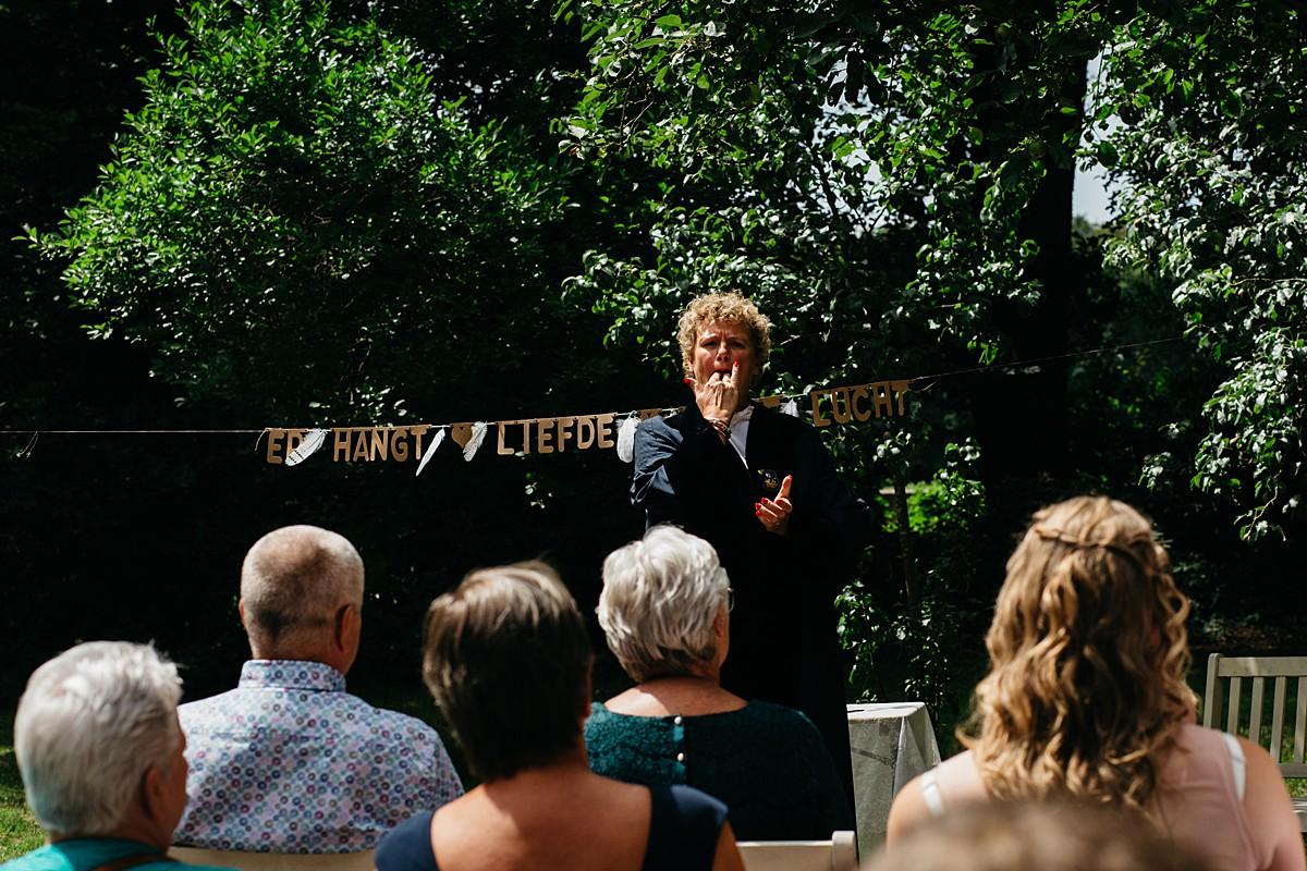 trouwambtenaar fluit op vingers tijdens start  huwelijksceremonie