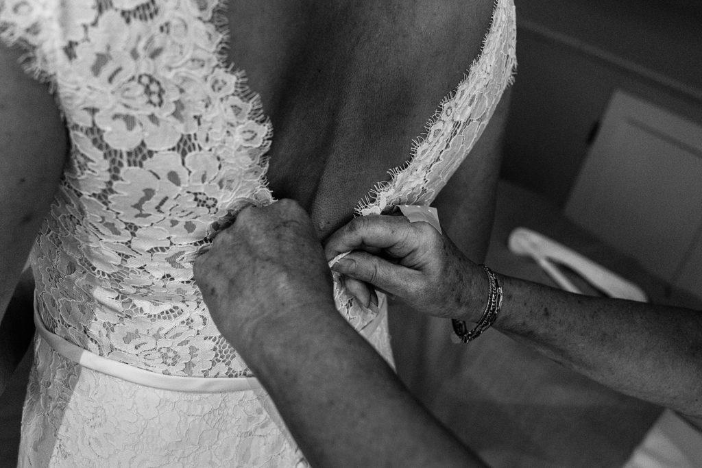 moeder helpt bruid met jurk