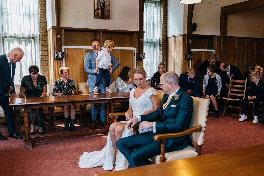bruidspaar gaat zitten voor de trouwceremonie