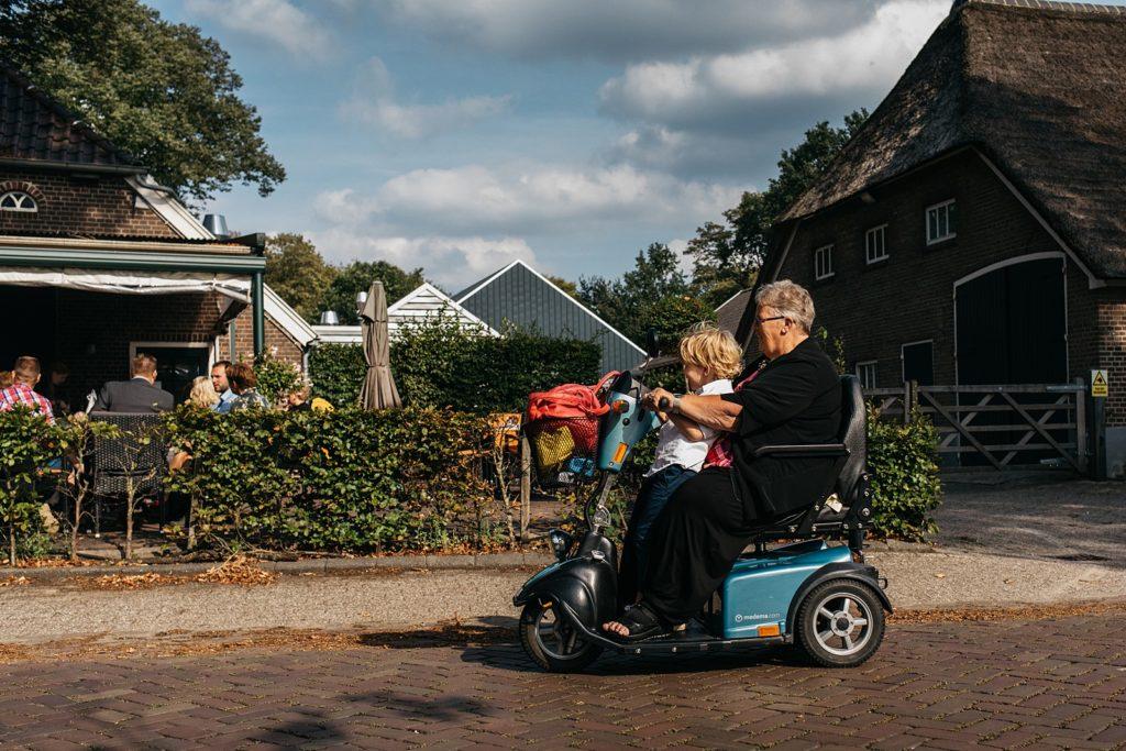 oma rijdt met kleinzoon op scootmobiel