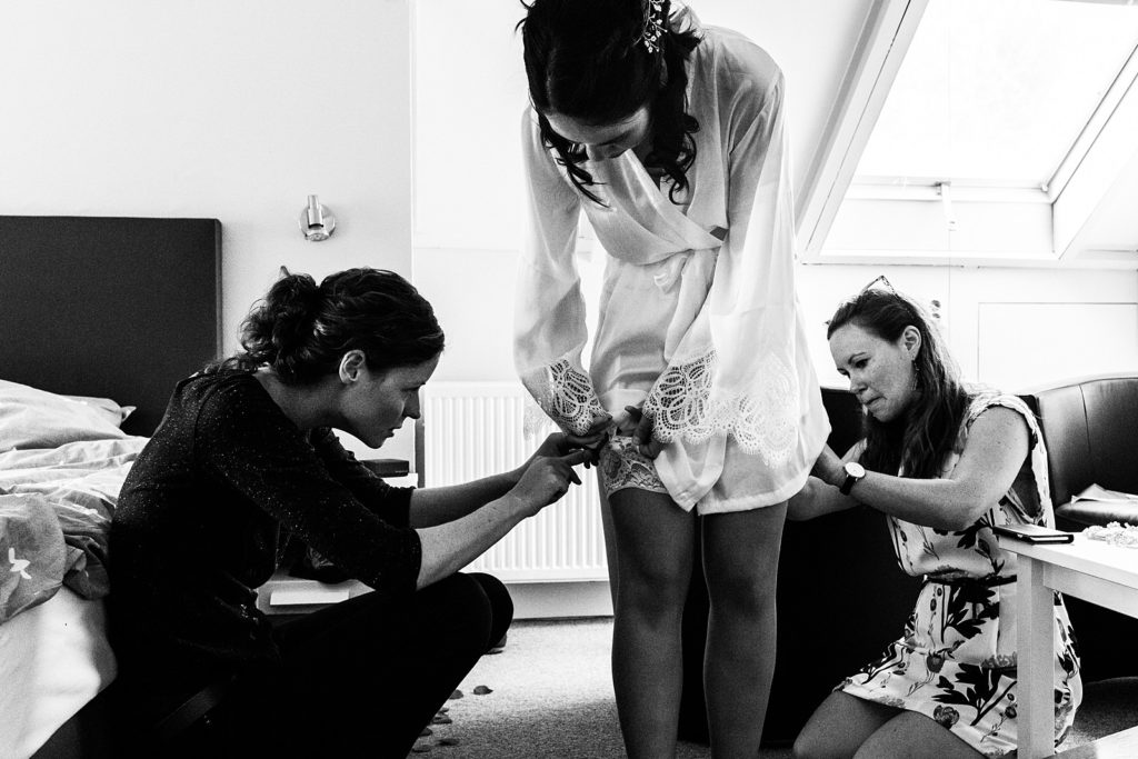 bruidsmeisjes helpen bruid met aankleden