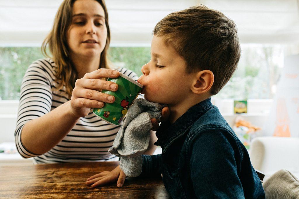 moeder geeft zoontje te drinken