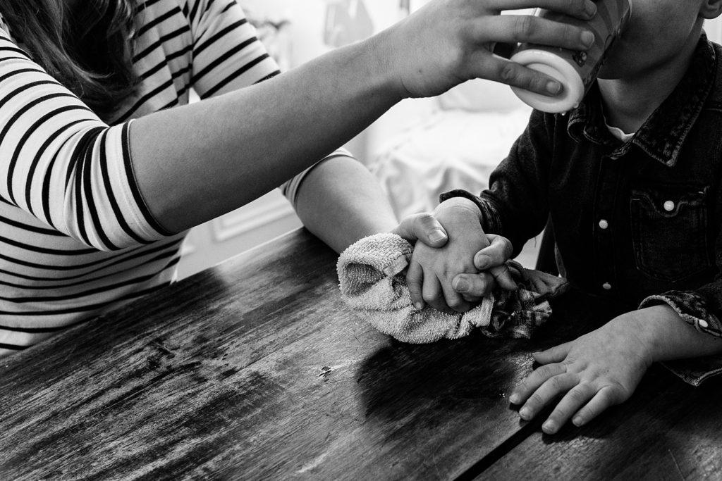 moeder houdt hand zoon vast