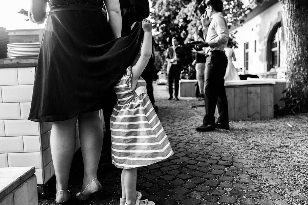 meisje verstopt zich onder rok van moeder