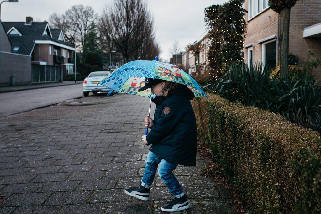 kind loopt met paraplu