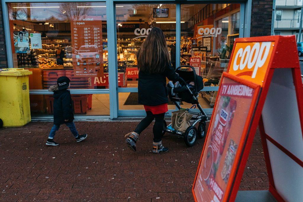 moeder loopt met kinderen de supermarkt binnen