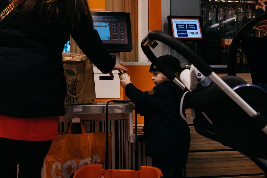 mama en zoon scannen boodschappen in supermarkt
