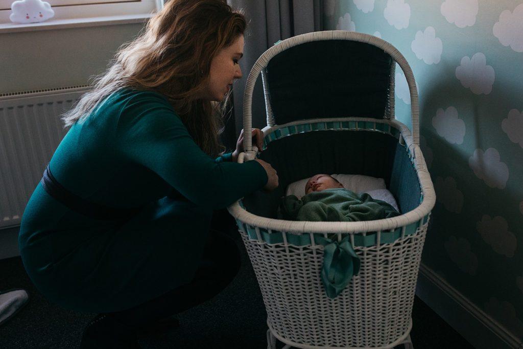 moeder bij het wiegje van newborn
