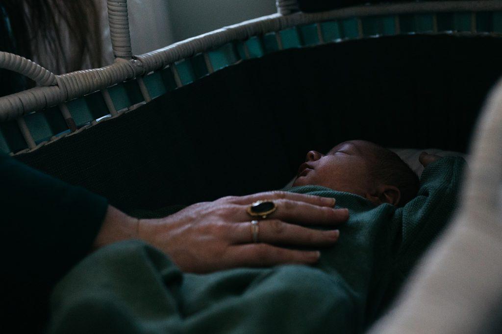 newborn in wiegje met moeder
