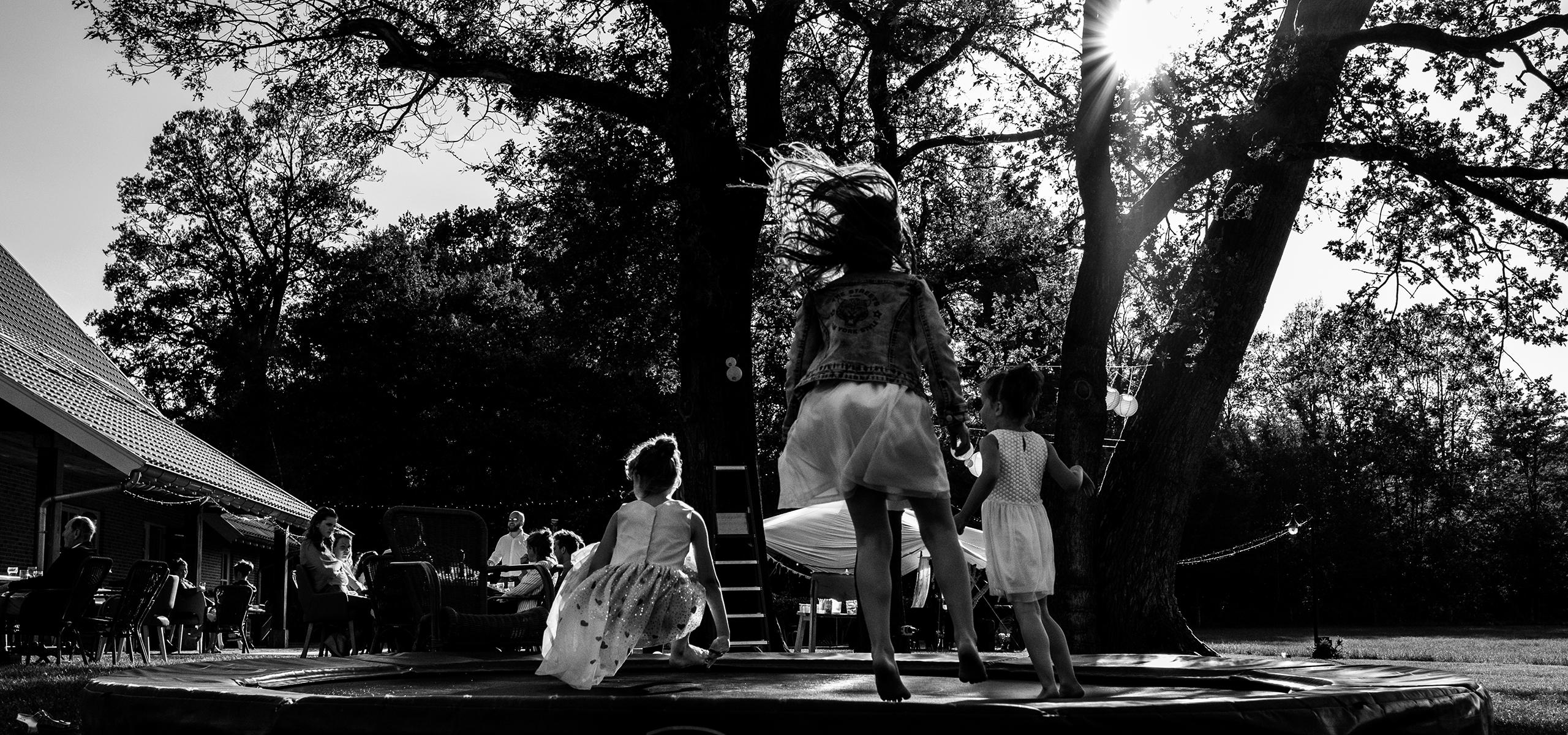 kinderen springen op trampoline gasten zitten aan tafel