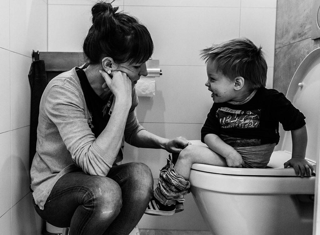 moeder helpt zoontje met naar de wc gaan