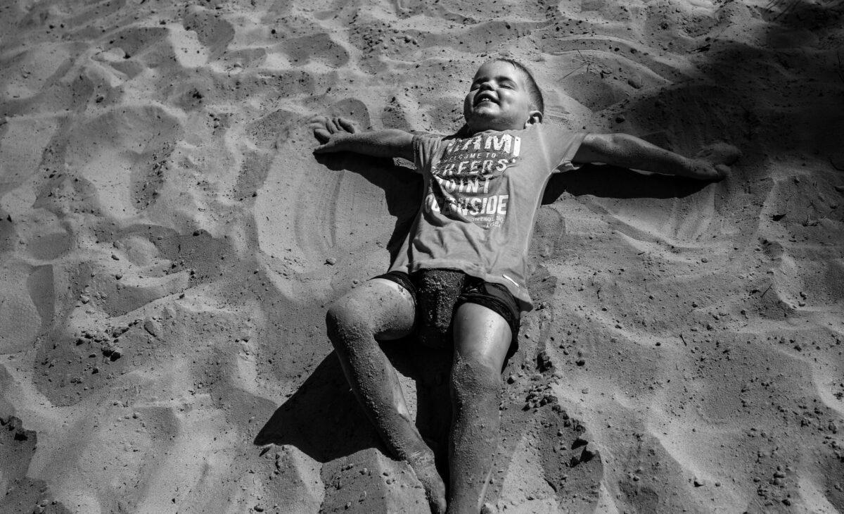 jongetje rolt door het zand